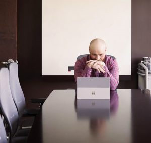 kris rivenburgh at end of conference table looking at microsoft surface laptop